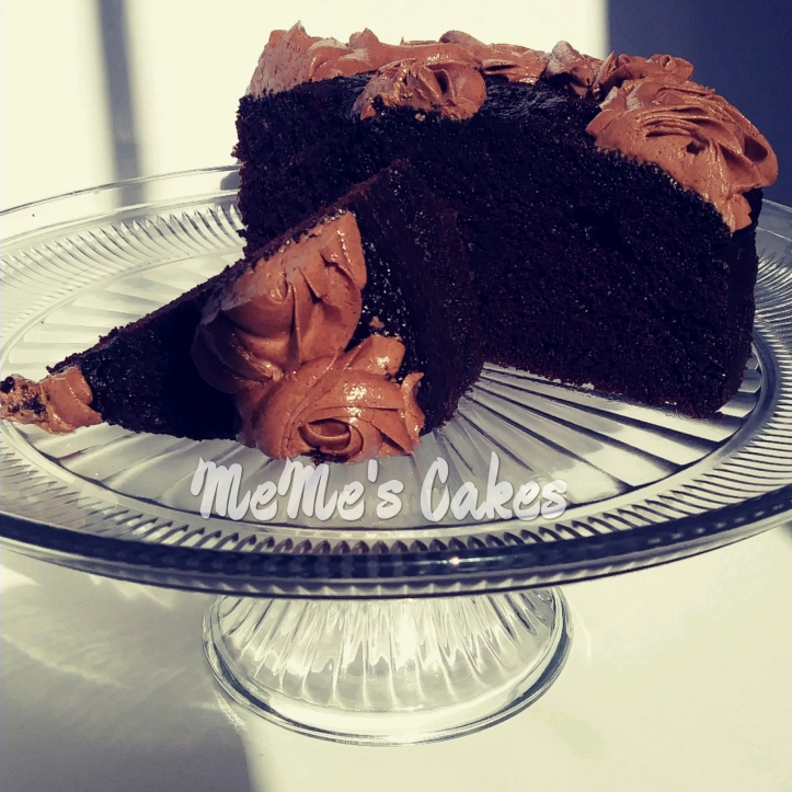 rich, dark, and moist chocolate cake on cake stand